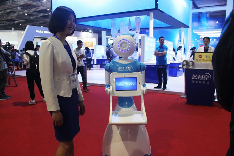 美博会上,高科技产品吸引了记者不小的注意。介绍产品的机器人。