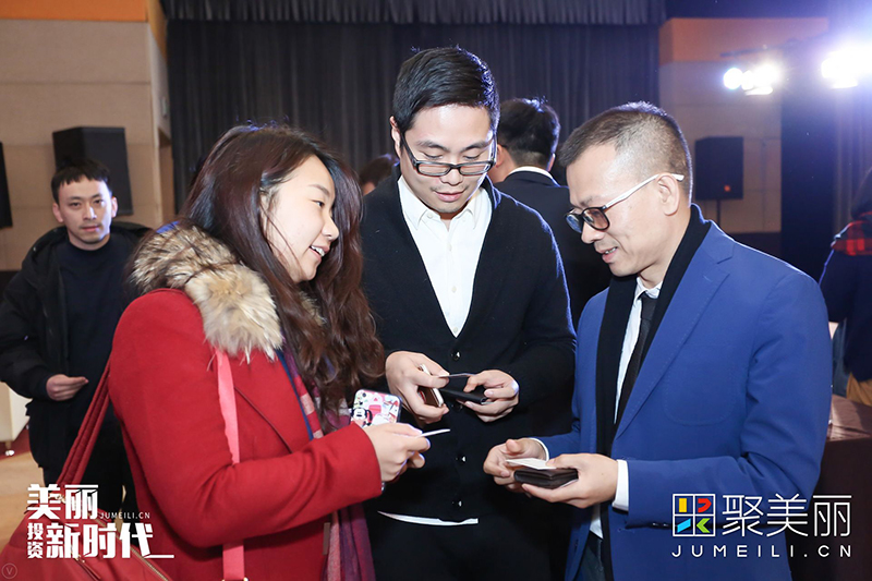 图为丹姿集团董事长兼总裁张楚标与参会人员交换联系方式。